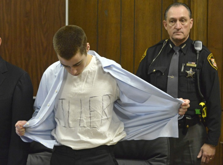"""T. J. Lane takes off his shirt to show a white T-shirt with the word """"Killer"""" spelled out on it at his sentencing hearing before Geauga County Judge David Fuhry in Cleveland, Ohio, March 19, 2013. Lane was sentenced to life without parole for killing three students in a shooting rampage at a high school in a small town east of Cleveland. (Duncan Scott/The News-Herald/Reuters)"""