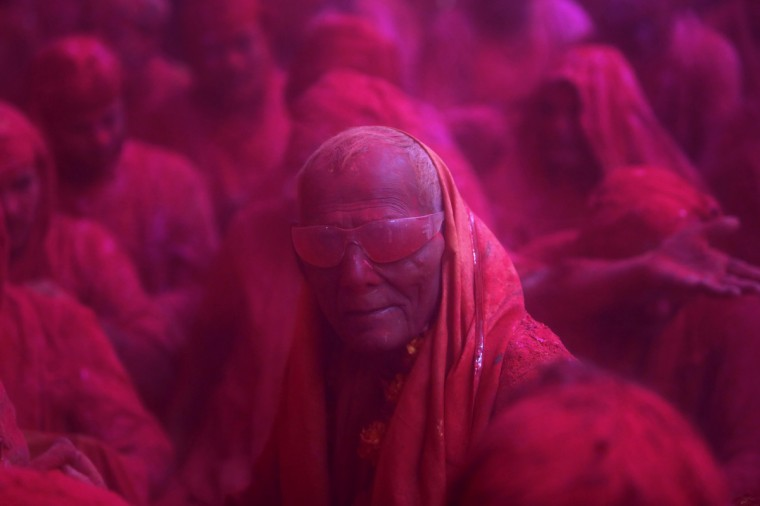"""A Hindu devotee looks on in a cloud of coloured powder inside a temple during """"Lathmar Holi"""" at the village of Barsana in the northern Indian state of Uttar Pradesh March 21, 2013. In a Holi tradition unique to Barsana and Nandgaon villages, men sing provocative songs to gain the attention of women, who then """"beat"""" them with bamboo sticks called """"lathis"""". Holi, also known as the Festival of Colours, heralds the beginning of spring and is celebrated all over India. (Vivek Prakash/Reuters)"""