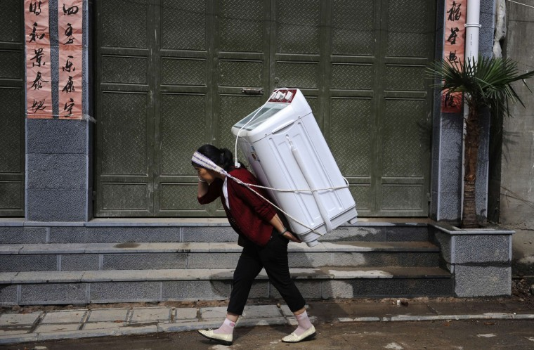 A woman carries home a washing machine in Dali, Yunnan province July 30, 2013. (Reuters)