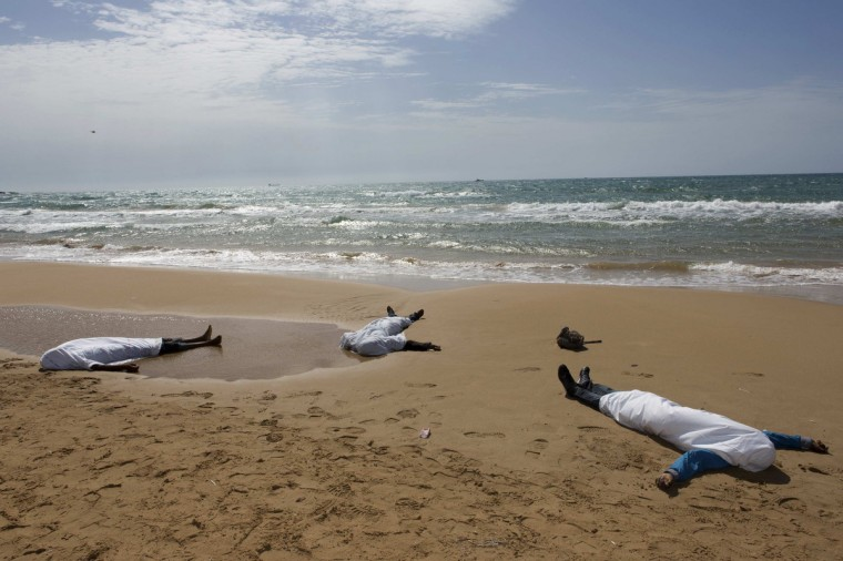 Bodies of migrants who drowned lie on the beach in the Sicilian village of Sampieri September 30, 2013. At least 13 people on a migrant boat arriving in Sicily drowned close to the coast near the eastern city of Ragusa, apparently after trying to disembark from their stranded vessel, Italian authorities said. Officials said the boat was carrying around 250 people but there was no immediate word on where they came from. (Gianni Mania/Reuters)