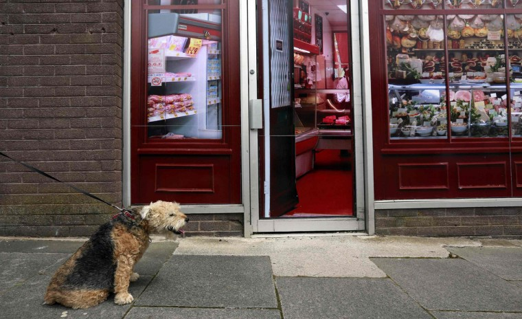 A man walks his dog past a vacant shop, with graphics pasted to the outside to make it look like a working butcher's shop, in the village of Belcoo, Northern Ireland June 3, 2013. Local councils in Northern Ireland have painted fake shop fronts and covered derelict buildings with huge billboards to hide the economic hardship being felt in towns and villages near the golf resort where G8 leaders have met in June. (Cathal McNaughton/Reuters)