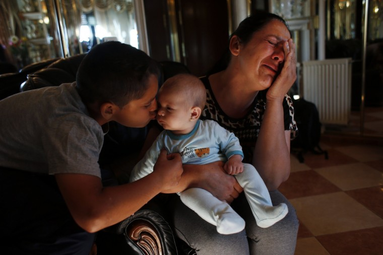"""Manuel Contreras, 11, kisses his niece Ainhoa, as his mother Carmen Acedo del Lago cries before learning that their eviction by the Municipal Housing and Land Company (EMVS) was postponed in Madrid June 4, 2013. Acedo del Lago, her husband, their five children, two sons-in-law and their four-month-old granddaughter have shared a social rental flat in northern Madrid since 2005. None of the adults in the family hold a steady job. The family fell behind on their monthly rent payments and were sent an eviction notice. """"How can they evict a family for owing 463 euros ($605)?"""" says Acedo del Lago. In the end, the eviction was postponed by the EMVS until June 25. (Susana Vera/Reuters)"""