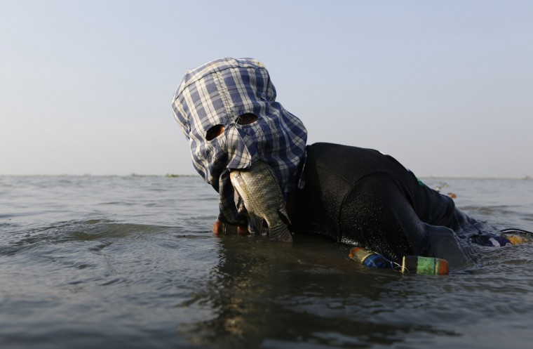 Fisherman Ompong Vargas, 39, wearing a facial mask made of fabric to protect his skin from getting darker, holds a fish in his mouth as he uses his hands to search for a net at Laguna de Bay in Taguig City, Metro Manila May 24, 2013. During the dry season, fishermen earn $2-$7 (70-300 pesos) per day. Men's beauty treatments are popular in the Philippines, part of a thriving market for male cosmetics in the Asia Pacific region. Some Filipino men go to great lengths to preserve their faces, from those who visit clinics to receive skin treatments, to fishermen who wear fabric masks while working to protect their skin from the sun. (Cheryl Ravelo/Reuters)