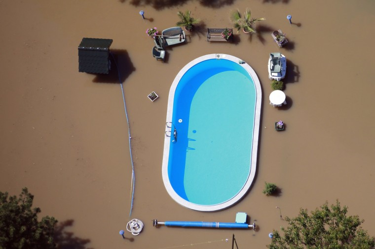 A garden with a swimming pool is inundated by the waters of the Elbe river during floods near Magdeburg in the federal state of Saxony Anhalt, June 10, 2013. Tens of thousands of Germans, Hungarians and Czechs were evacuated from their homes as soldiers raced to pile up sandbags to hold back rising waters in the region's worst floods in a decade. (Thomas Peter/Reuters)