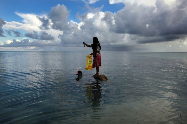 Binata Pinata stands on top of a rock holding a fish her husband Kaibakia (L) has just caught off Bikeman islet, located off South Tarawa in the central Pacific island nation of Kiribati May 25, 2013. Kiribati consists of a chain of 33 atolls and islands that stand just metres above sea level, spread over a huge expanse of otherwise empty ocean. With surrounding sea levels rising, Kiribati's President Anote Tong has predicted his country will likely become uninhabitable in 30-60 years because of inundation and contamination of its freshwater supplies. (David Gray/Reuters)