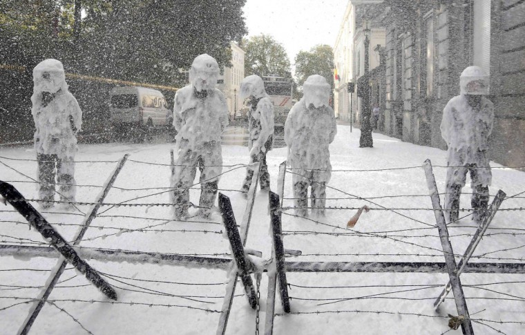 Belgian riot police are covered with foam sprayed by Belgian firefighters during a protest for better work conditions in central Brussels October 7, 2013. (Yves Herman/Reuters)