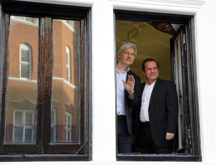 WikiLeaks founder Julian Assange waves from a window with Ecuador's Foreign Affairs Minister Ricardo Patino (R) at Ecuador's embassy in central London June 16, 2013. Assange sought asylum in the embassy on June 19, 2012, in an attempt to avoid extradition to Sweden. (Chris Helgren/Reuters)