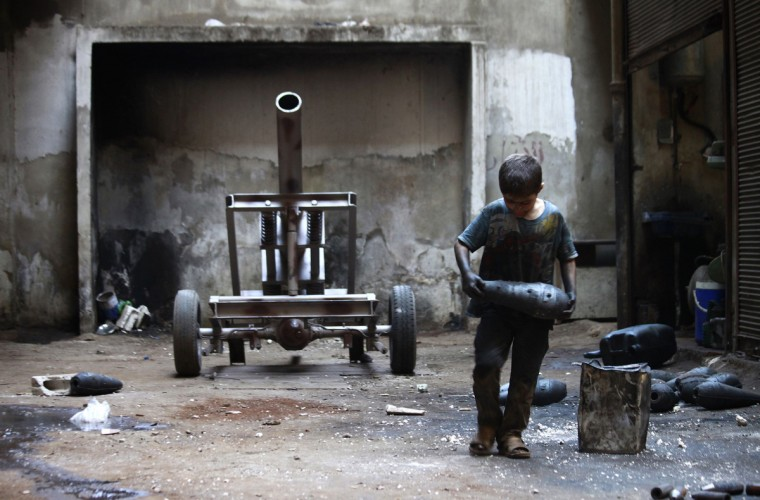 Issa, 10 years old, carries a mortar shell in a weapons factory of the Free Syrian Army in Aleppo, September 7, 2013. Issa works with his father in the factory for ten hours every day except on Fridays. (Hamid Khatib/Reuters)