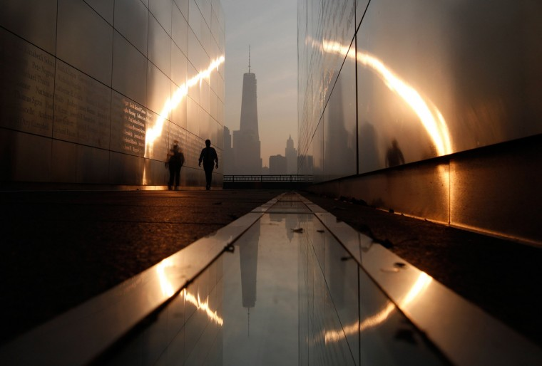 A man walks through the 9/11 Empty Sky memorial at sunrise across from New York's Lower Manhattan and One World Trade Center in Liberty State Park in Jersey City, New Jersey, September 11, 2013. Americans will commemorate the 12th anniversary of the September 11 attacks with solemn ceremonies and pledges to not forget the nearly 3,000 killed when hijacked jetliners crashed into the World Trade Center, the Pentagon, and a Pennsylvania field. (Gary Hershorn/Reuters)