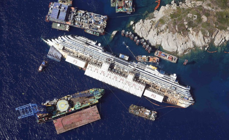 An aerial view shows the Costa Concordia as it lies on its side next to Giglio Island taken from an Italian navy helicopter August 26, 2013. The giant vessel, which has lain partly submerged in shallow waters off the Tuscan island of Giglio since the accident in January 2012, will be rolled off the seabed and onto underwater platforms. (Alessandro Bianchi/Reuters)
