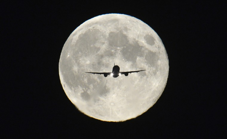 """A passenger aircraft, with the full """"Harvest Moon"""" seen behind, makes its final approach to landing at Heathrow Airport in west London, September 19, 2013. The Harvest Moon is a traditional name for the full moon that is closest to the autumn equinox, and at a traditional period where farmers would be harvesting crops. The moon's rise time and angle of path give the illusion that the Harvest Moon is both closer, larger and brighter; though actually it is not. (Toby Melville/Reuters)"""