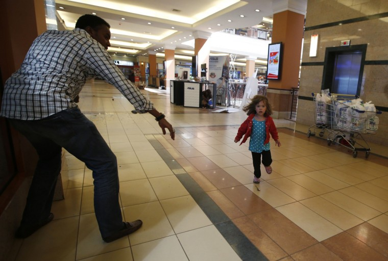 A child runs to safety as armed police hunt gunmen who went on a shooting spree at Westgate shopping centre in Nairobi September 21, 2013. The gunmen stormed a shopping mall in Nairobi killing at least 20 people in what Kenya's government said could be a terrorist attack, and sending scores fleeing into shops, a cinema and onto the streets in search of safety. Sporadic gun shots could be heard hours after the assault started as soldiers surrounded the mall and police and soldiers combed the building, hunting down the attackers shop by shop. Some local television stations reported hostages had been taken, but there was no official confirmation. (Goran Tomasevic/Reuters)