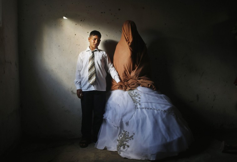 Young Palestinian groom Ahmed Soboh, 15 and his bride Tala, 14, stand inside Tala's house which was damaged during an Israeli strike in 2009, during their wedding party in the town of Beit Lahiya, near the border between Israeli and northern Gaza Strip September 24, 2013. (Mohammed Salem/Reuters)