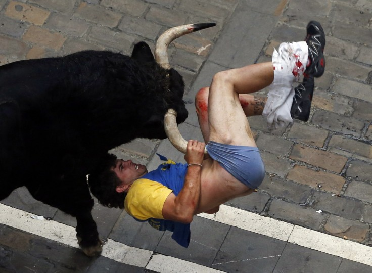 A runner gets gored by a bull on Estafeta Street during the sixth running of the bulls at the San Fermin festival in Pamplona July 12, 2013. The runner, a 31-year-old man from Castellon, Spain, identified by local media as Diego Miralles, was gored three times. (Susana Vera/Reuters)