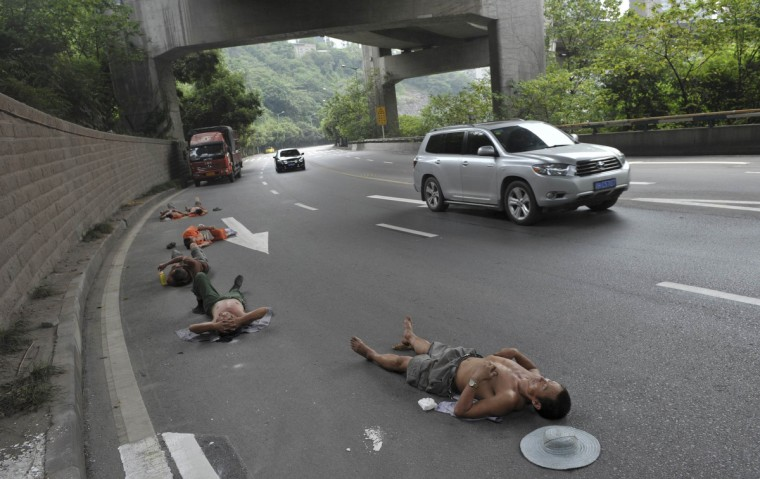 Laborers who work nearby nap on a road as cars drive past in Chongqing Municipality, July 23, 2013. (Reuters)