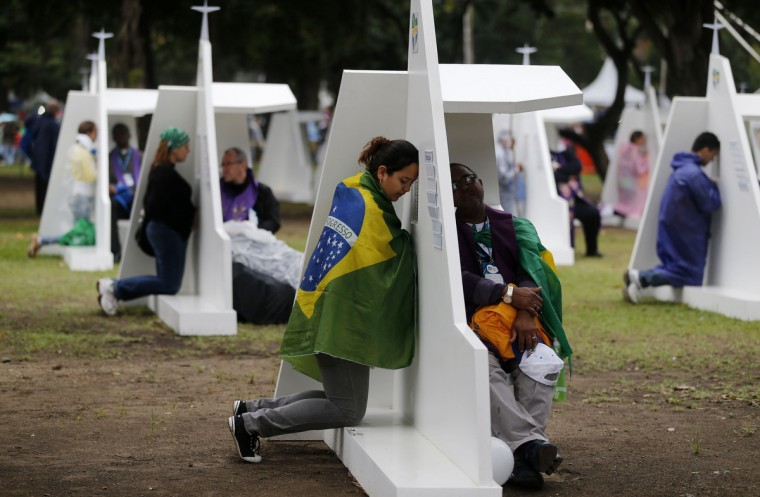A woman draped in the Brazilian national flag gives her confession at confessional booths set up at Quinta da Boa Vista park for World Youth Day in Rio de Janeiro July 24, 2013. (Sergio Moraes/Reuters)