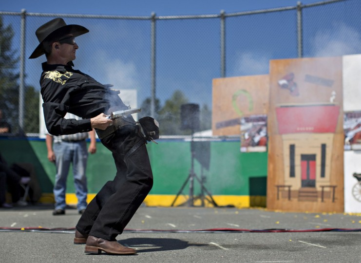 "Nick ""The Quick"" Nica of Montreal, Quebec, draws and fires his single action revolver while competing in the Canadian Open Fast Draw Championships in Aldergrove, British Columbia July 21, 2013. The present-day Fast Draw competition was born from the Hollywood myth of the Western gunfighter, and the idea is to draw a single action revolver from a holster, and cock, fire and hit a designated target in the shortest possible time. No live ammunition is ever used, only blank cartridges or wax bullets. The targets are either a metal silhouette used with wax bullets or balloons that burst from the muzzle blast from the blank cartridges. A light atop the timer signals the competitor when to fire and once the target is hit, it turns the timer off, measuring the speed to thousandths of a second. (Andy Clark/Reuters)"