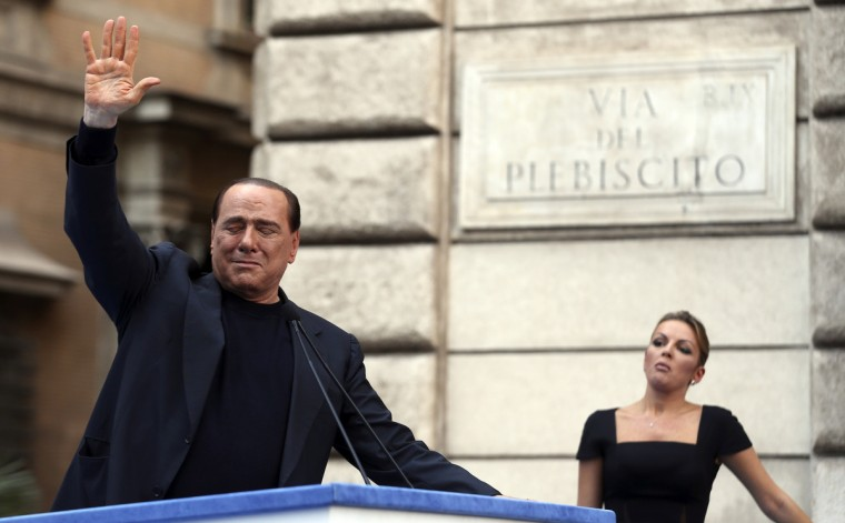 Former Italian Prime Minister Silvio Berlusconi waves to supporters as his girlfriend Francesca Pascale looks on during a rally to protest his tax fraud conviction, outside his palace in central Rome August 4, 2013. Tensions in Italy's squabbling coalition heightened ahead of a rally by supporters of Berlusconi in Rome in protest at a tax fraud conviction that threatens his future in politics and the fragile government. (Alessandro Bianchi/Reuters)