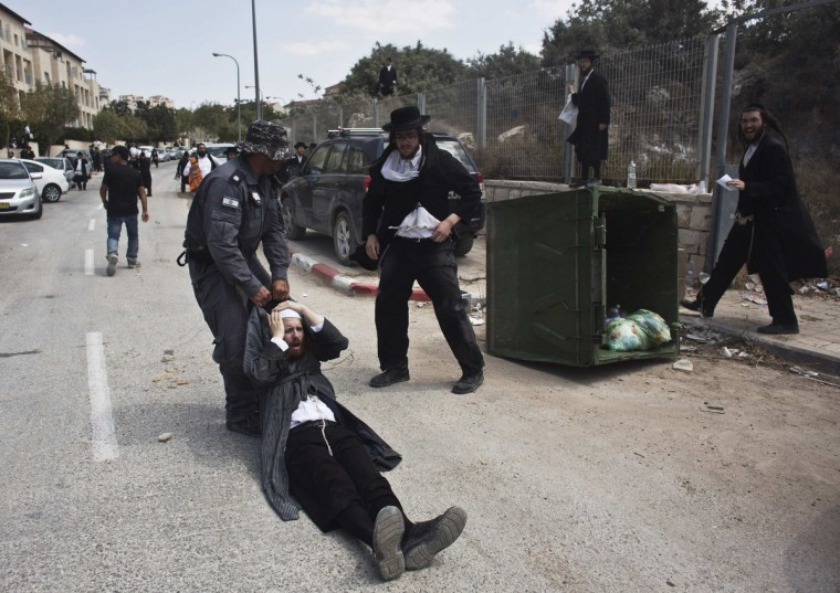 An Israeli policeman drags an ultra-Orthodox man during clashes in the town of Beit Shemesh, near Jerusalem August 12, 2013. An Israeli police spokesperson said some 21 ultra-Orthodox protesters were detained in the town during clashes with police after a group of them broke into a construction site to prevent work from taking place at the site they believe contains ancient graves. (Nir Elias/Reuters)