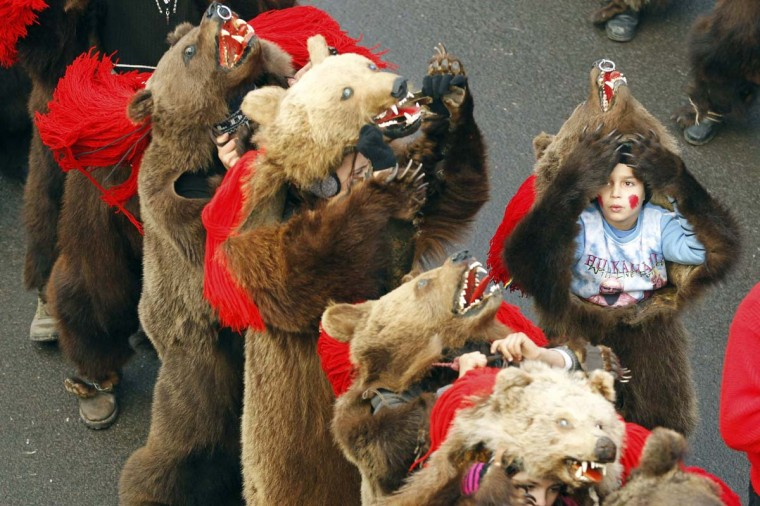 """Dancers from Romania's northeastern region of Moldova perform the """"bear"""" dance, a ritual for good luck in the New Year, during a traditional parade in Comanesti, 300 km (186 miles) northeast of Bucharest December 30, 2013. In pre-Christian rural traditions dancers used to tour from house to house in villages while singing and dancing to ward off evil. (Bogdan Cristel/Reuters)"""
