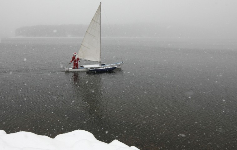 """A member of the """"Skipper"""" yacht club dressed as Santa Claus, sails his trimaran to mark the ending of the sailboat season during heavy snowfall at an air temperature of above minus 8 degrees Celsius (17.6 Fahrenheit) on the Yenisei River, outside Russia's Siberian city of Krasnoyarsk. (Ilya Naymushin/Reuters)"""