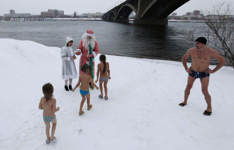 """Young members of the """"Krepysh"""" family winter swimming club visit Father Frost and Snegurochka, the Russian equivalents of Santa Claus and Snow Maiden, during a New Year celebration on the banks of the Yenisei River in Russia's Siberian city of Krasnoyarsk, December 29, 2013. Picture taken December 29, 2013. (Ilya Naymushin/Reuters)"""