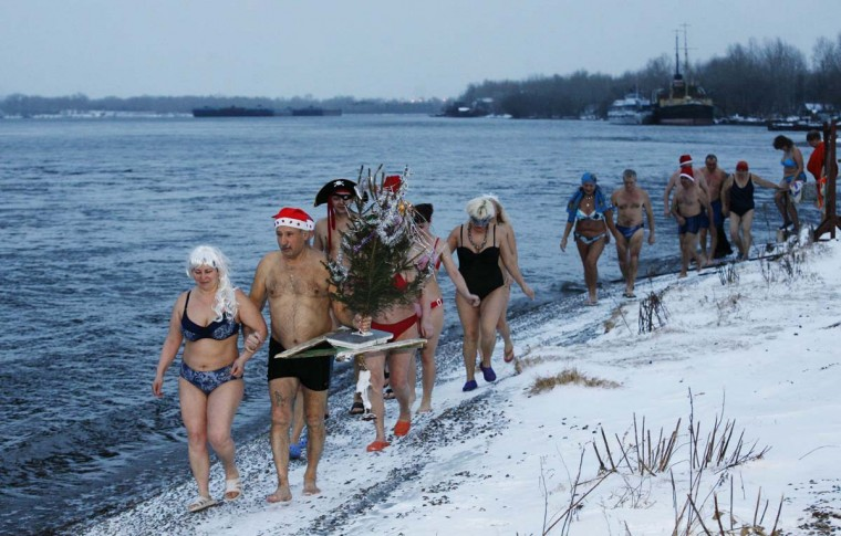 """Members of the """"Cryophil"""" winter swimming club walk along the Yenisei River holding a Christmas tree, during a New Year celebration in air temperatures of minus 5 degrees Celcius (23 degrees Fahrenheit) in Russia's Siberian city of Krasnoyarsk, December 29, 2013. Picture taken December 29, 2013. (Ilya Naymushin/Reuters)"""