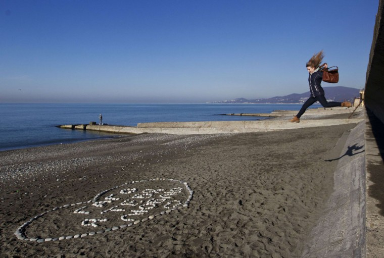 A woman jumps down onto the beach in the Adler district of the Black Sea resort city of Sochi, December 24, 2013. Sochi will host the 2014 Winter Olympics in February. (REUTERS/Maxim Shemetov)