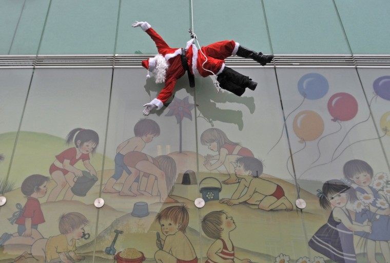 A member of the special police force dressed in a Santa suit descends from the roof of a pediatric clinic in Ljubljana, as part of a Christmas performance for patients of the clinic(Srdjan Zivulovic/Reuters)