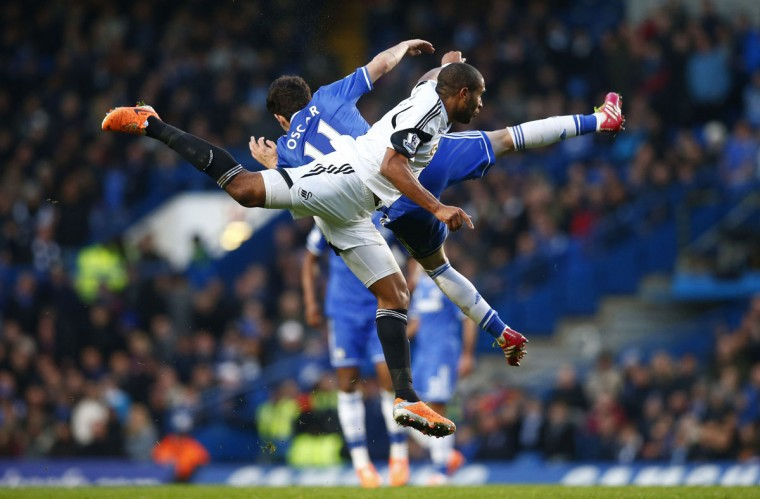 Oscar (L) of Chelsea and Ashley Williams of Swansea fall after jumping for the ball during their English Premier League soccer match at Stamford Bridge, London, December 26, 2013. (REUTERS/Andrew Winning)