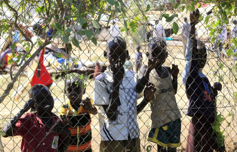 Children displaced by recent fighting in South Sudan react to the camera from behind a fence at the United Nations Mission in Sudan (UNAMIS) facility in Jabel, on the outskirts of capital Juba December 23, 2013. South Sudan President Salva Kiir said on Tuesday government troops have take control of the Jonglei state capital Bor, a key town which rebels loyal to former Vice President Riek Machar seized last week. Picture taken December 23, 2013. (REUTERS/James Akena)