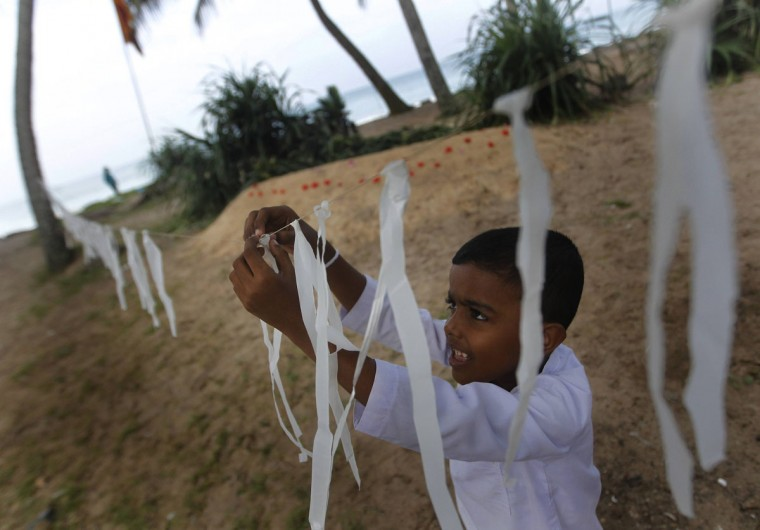 A boy hangs strips of white polythene, the colour being a symbolism for death in Buddhism, near a mass grave for victims, who died when their train was swept from its tracks by the 2004 tsunami, during a memorial in Peraliya, about 90 km (56 miles) south of Colombo December 26, 2013. Hundreds of memorial events were held across Asia in memory of the towering waves that crashed ashore with little warning on December 26, 2004, killing around 230,000 people in Indonesia, Sri Lanka, India, Thailand and nine other countries. More than half the victims were Indonesians; with Sri Lanka and India next worst hit. (REUTERS/Dinuka Liyanawatte)
