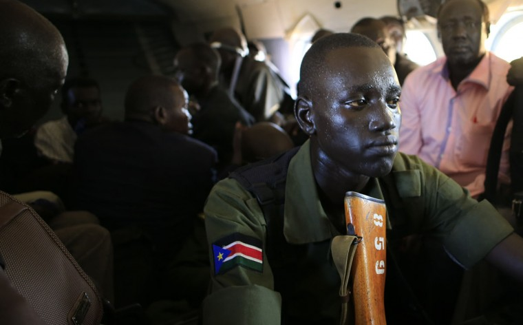 A South Sudan army soldier sweats as he holds his weapon during a flight from the capital Juba to Bor town, 180 km (108 miles) northwest from capital, December 25, 2013. South Sudan President Salva Kiir said on Tuesday government troops have take control of the Jonglei state capital Bor, a key town which rebels loyal to former Vice President Riek Machar seized last week. Picture taken December 25, 2013. (REUTERS/James Akena)