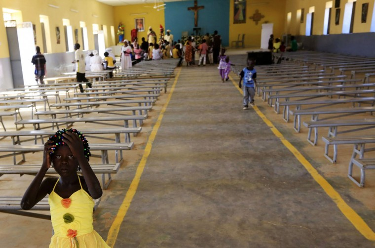 A South Sudanese girl living in the North reacts during Christmas celebrations at a Catholic church in the Umbada locality of Omdurman, December 25, 2013. (Mohamed Nureldin Abdallah/Reuters)