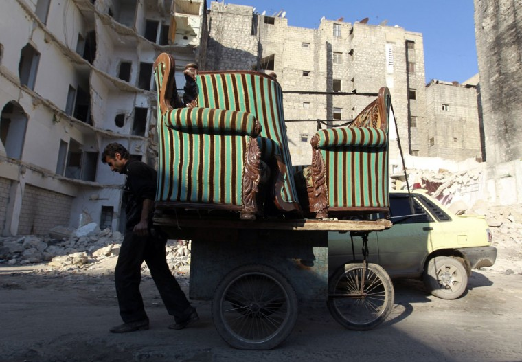 A man transports furniture on a cart, as he moves house from an area controlled by the Free Syrian Army to one controlled by the Syrian regime along a street in Aleppo's Bustan al-Qasr neighbourhood December 24, 2013. (REUTERS/Jalal Alhalab)