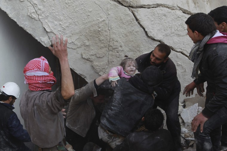A child is rescued from under the rubble of a collapsed building in the Maysar neighbourhood of Aleppo December 28, 2013. The building collapsed after two air strikes in the neighbourhood by forces loyal to Syria's President Bashar al-Assad on Saturday, activists said. (REUTERS/Jalal Alhalabi)