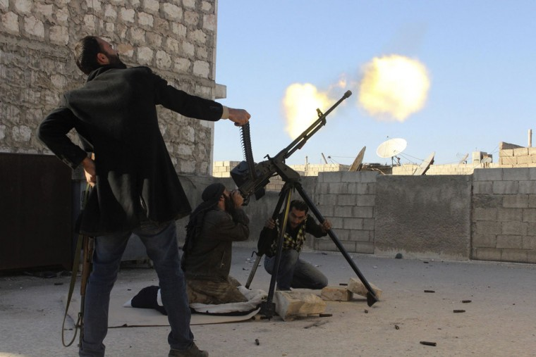A Free Syrian Army fighter holds up an ammunition belt as his fellow fighter fires on a helicopter belonging to the Syrian regime in Aleppo's Bustan al-Basha district December 6, 2013. (REUTERS/Molhem Barakat)