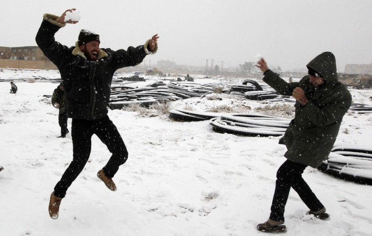 Free Syrian Army fighters play with snow in Raqqa, eastern Syria, December 11, 2013. Picture taken December 11, 2013. (REUTERS/Nour Fourat)