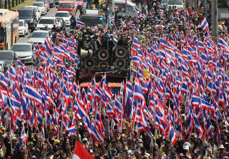 Anti-government protesters hold Thai national flags as they march towards the Department of Special Investigation (DSI) in Bangkok December 23, 2013. The Thai baht plumbed its lowest level in almost four years on Monday as a political crisis grew more intractable, with anti-government protesters attempting to stop candidates from registering for a February election. (Kerek Wongsa/Reuters)