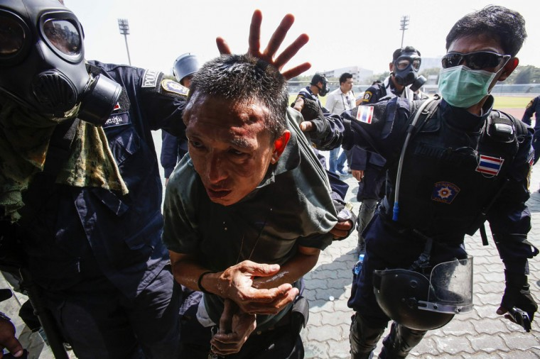 Riot policemen escort an anti-government protester during clashes at the Thai-Japan youth stadium in central Bangkok December 26, 2013. Thai police fired teargas at anti-government protesters in the capital Bangkok on Thursday after demonstrators tried to disrupt planning for a February election, the first such incident in nearly two weeks. (REUTERS/Athit Perawongmetha)