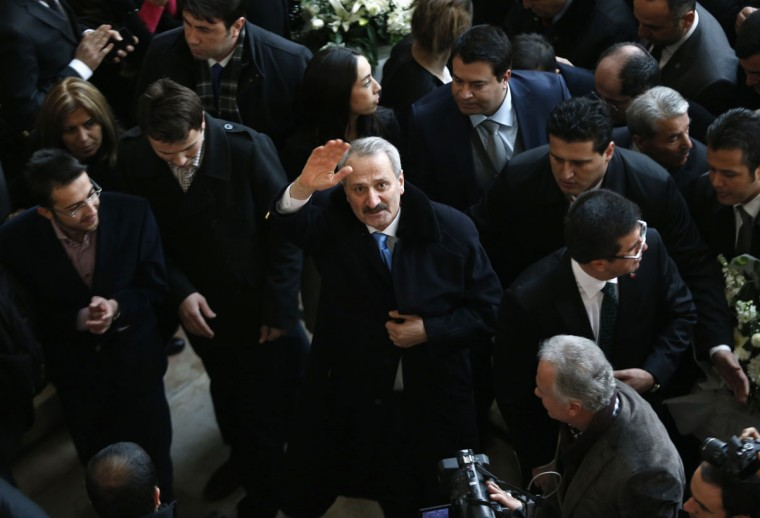 """Turkey's outgoing Economy Minister Zafer Caglayan waves as he arrives at a handover ceremony in Ankara December 26, 2013. Turkey's opposition accused scandal-hit Prime Minister Tayyip Erdogan on Thursday of trying to rule via a secretive """"deep state"""", after a cabinet reshuffle that would tighten controls on police already beleaguered by government-ordered purges. (REUTERS/Umit Bektas)"""