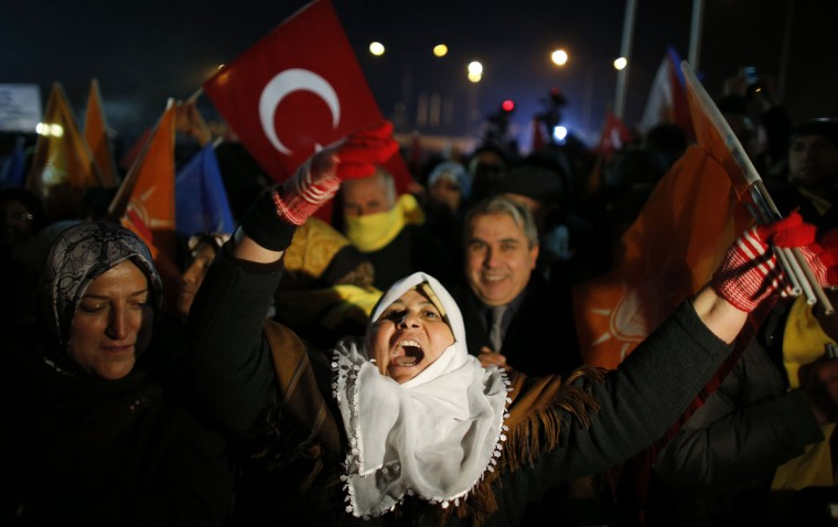 Supporters of Turkey's Prime Minister Tayyip Erdogan shout slogans and wave flags as they gather to welcome his arrival at Esenboga Airport in Ankara December 24, 2013. Turkey's President Abdullah Gul pledged on Tuesday there would be no cover-up in a high-level corruption case, despite a government-ordered purge of police investigating it that drew protests at home and a caution from the European Union. The week-long scandal, which erupted with the arrest for graft of 24 people, including the chief of a state-run bank and the sons of two ministers, pits Erdogan against the judiciary and has rattled investor confidence. (REUTERS/Umit Bektas)