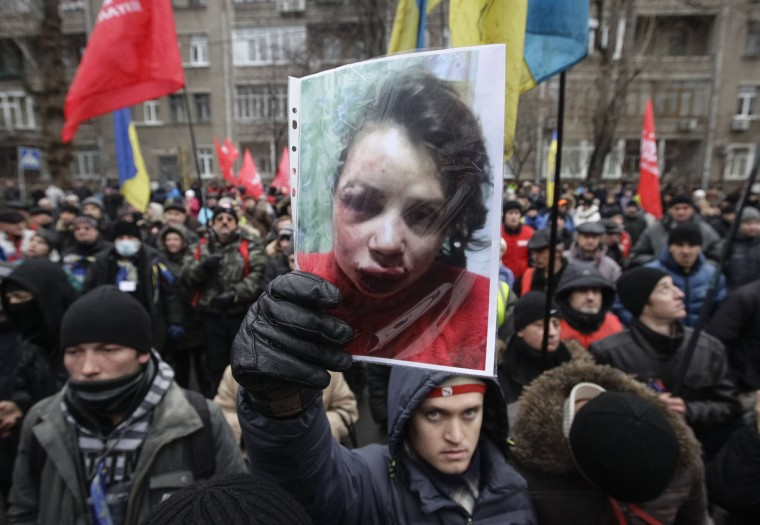 A protester holds a picture of journalist Tetyana Chornovil, who was beaten and left in a ditch just hours after publishing an article on the assets of top government officials, during a protest rally in front of the Ukrainian Ministry of Internal Affairs in Kiev, December 25, 2013. Chornovil, a prominent activist who has given speeches at recent anti-government protests, told police her car was stopped by a vehicle just after midnight. A group of unidentified men got out and broke the rear window of her car. (Stringer/Reuters)