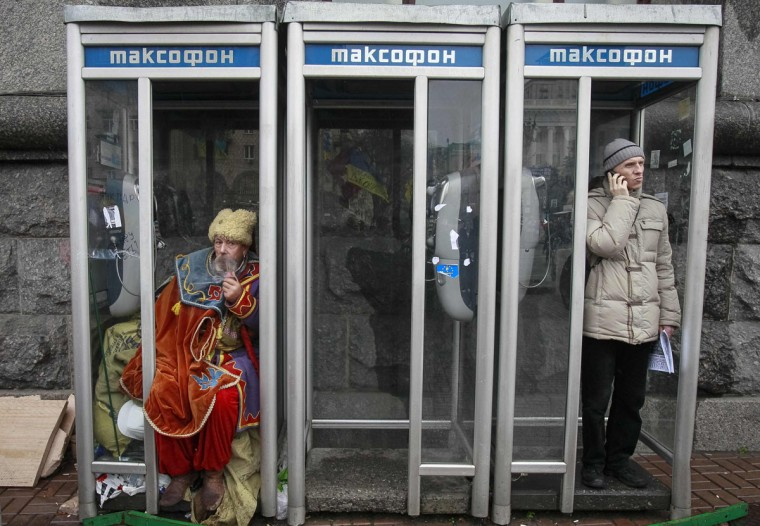 A man dressed in traditional Ukrainian Cossack clothes smokes in a phonebooth during a rally to support EU integration in Kiev December 6, 2013. Ukrainian President Viktor Yanukovich was flying to Russia on Friday to meet Vladimir Putin, a news agency reported, seeking aid to shore up a creaking economy while protesters back home, opposed to his U-turn away from Europe, defied police. (REUTERS/Gleb Garanich)