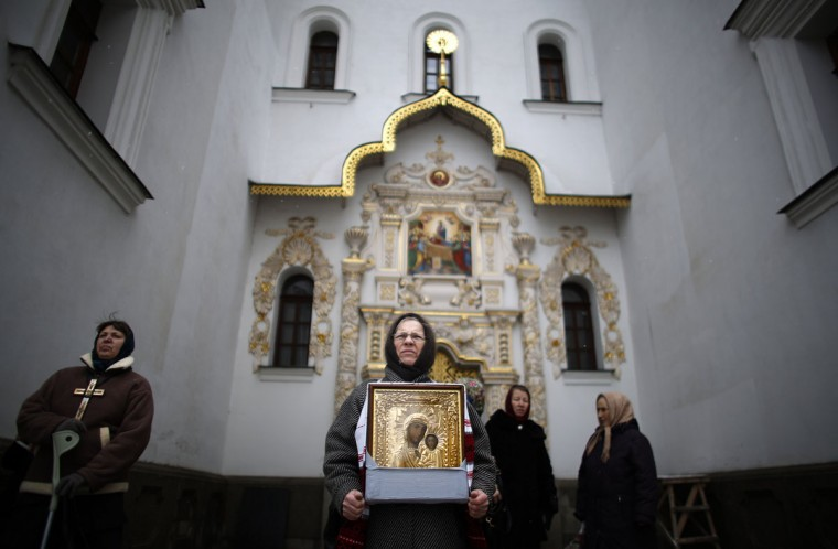 A believer holds an icon of the Virgin Mary in front of Kievo-Pecherskaya Lavra Cathedral during a procession of relics and pictures of Eastern Orthodox saints commemorating the icon of St. Nicholas the Drenched, in Kiev December 6, 2013. (REUTERS/Stoyan Nenov)