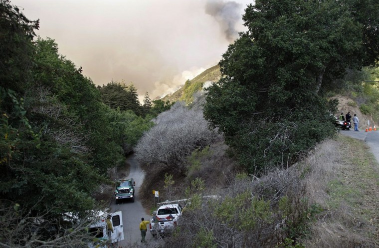 Police and fire vehicles sit at the entrance to a canyon during a wild fire in Big Sur, California, December 17, 2013. A wildfire that erupted in a scenic stretch of California's central coastline late Sunday night has destroyed at least 15 homes and forced many residents to evacuate, county and fire officials said. (REUTERS/Michael Fiala)