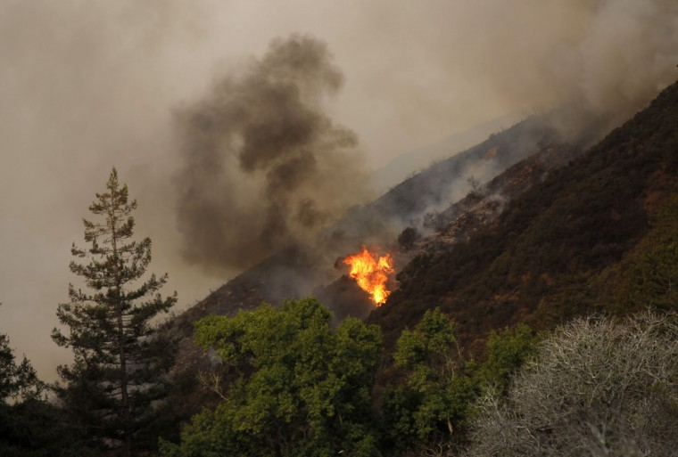 A blaze flares up during a wild fire in Big Sur, California, December 17, 2013. A wildfire that erupted in a scenic stretch of California's central coastline late Sunday night has destroyed at least 15 homes and forced many residents to evacuate, county and fire officials said. (REUTERS/Michael Fiala)