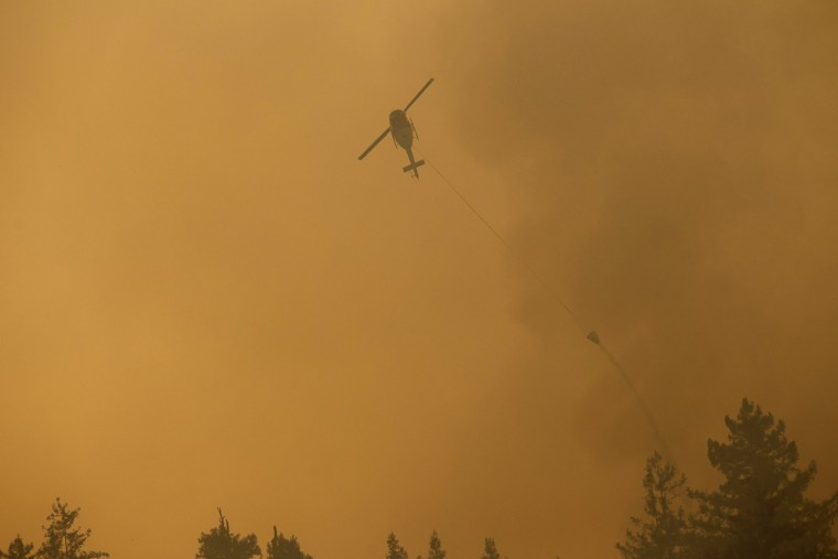 A helicopter drops ocean water on a wildfire burning on Pfeiffer Ridge in Big Sur, California, December 17, 2013. The wildfire erupted in a scenic stretch of California's central coastline late Sunday night has destroyed at least 15 homes and forced many residents to evacuate, county and fire officials said. (REUTERS/Michael Fiala)
