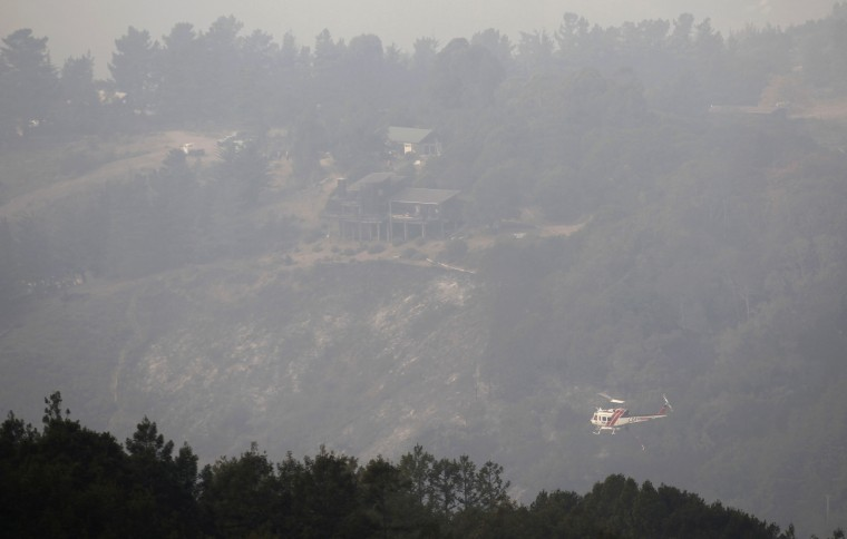 A helicopter drops ocean water on a wildfire burning on Pfeiffer Ridge in Big Sur, California, December 17, 2013. The wildfire that erupted in a scenic stretch of California's central coastline late Sunday night has destroyed at least 15 homes and forced many residents to evacuate, county and fire officials said. (REUTERS/Michael Fiala)