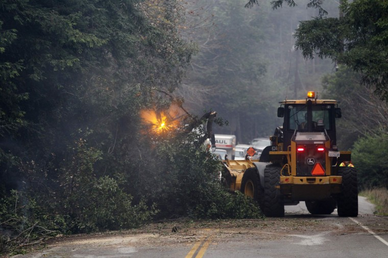 A loader removes a smoldering tree that fell on Highway 1 during a wildfire in Big Sur, California, December 17, 2013. Crews battling the wildfire along central California's scenic Big Sur coastline were on guard against a possible shift in winds on Tuesday, after the blaze destroyed at least 15 dwellings and forced 100 people to flee their homes, fire and county officials said. (REUTERS/Michael Fiala)